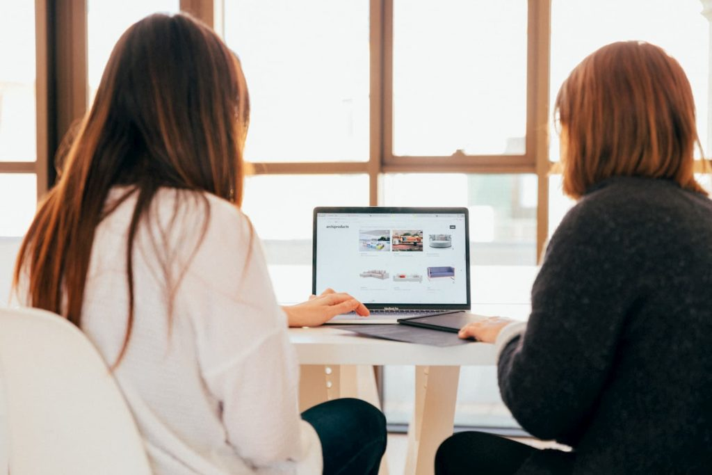 Two ladies searching for office space online